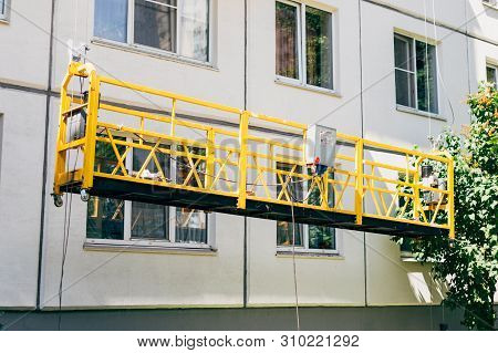 Yellow empty suspended construction cradle. Facing, repair, maintenance, painting the building in sunny summertime. poster