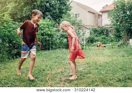 poster of Kids friends boy girl splashing with gardening hose sprinkler on backyard on summer day. Children playing with water outside at home yard. Candid authentic real life moment of funny family activity