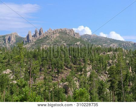Wide Landscape View With Rock Formations In The Distance Seen Along Needles Highway At Custer State