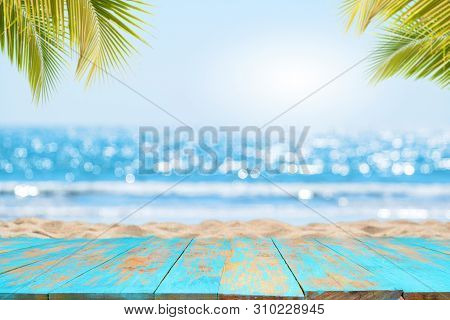 Top Of Wood Table With Seascape And Palm Leaves, Blur Bokeh Light Of Calm Sea And Sky At Tropical Be