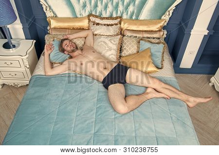 Bohemian Relax. Man Attractive Muscular Body Relax On King Size Bed. Luxury Apartment Hotel. Guy Rel