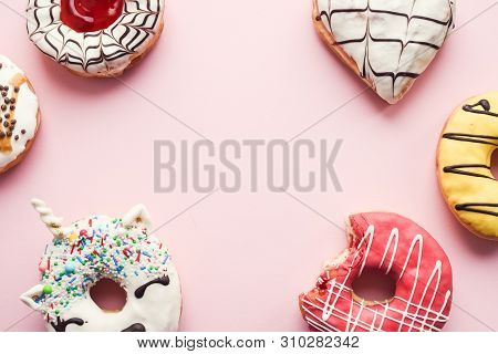 Pink Frosted Donut With Bite Missing With Assortment Donuts On Pink Background With Place For Text.