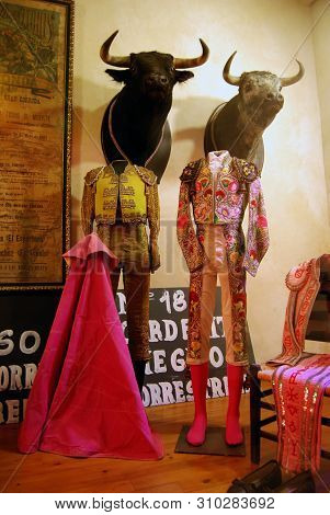Ronda, Spain - May 5, 2008 - Elaborate Matador Costumes On Display With Bulls Heads Mounted On The W