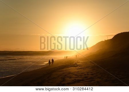 Elderly Couple Walking On Afternoon Sunset Beach, Mossel Bay, South Africa
