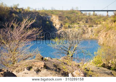 Blue Lake. Stony Sandy Steep Bank Of The Iron Ore Quarry, Lake With Emerald Water. Natural Landscape