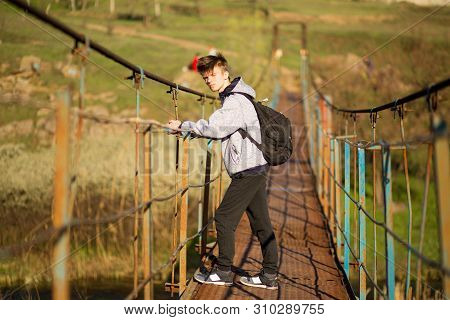 Traveling Man Crossing Through Hanging Bridge In Good Sunny Day Over The River