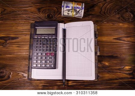 Opened Notepad, One Hundred Dollar Banknotes, Scientific Calculator And Pencil On Rustic Wooden Tabl