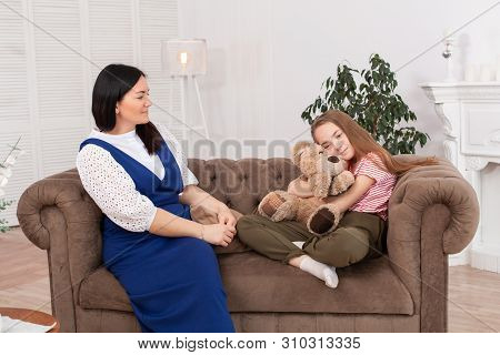 Mom And Daughter Spend Time Together, Sit On The Couch And Chat. Leisure Mothers And Daughters. Sad