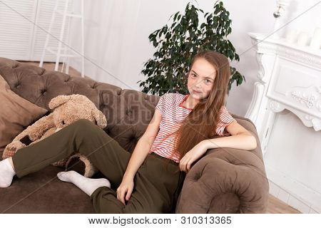 Portrait Of A Beautiful Redhead Teen Girl. Cute Girl Sitting On The Sofa, Smiling And Looking At The
