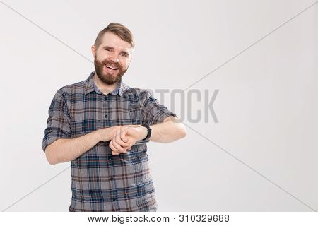 Happy Young Man In Plaid Shirt Pointing On Wrist Watch Over White Background With Copy Space