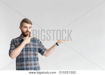 Serious Young Hipster Man With A Mustache Posing On A White Background And Pointing On Right. Concep
