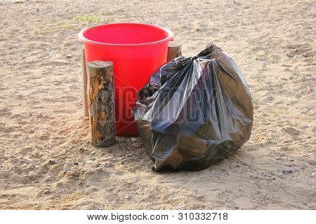 Red Plastic Garbage Collection Tank And Black Plastic Garbage Bag Full Of Garbage Nearby. Garbage Co