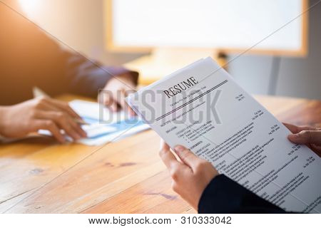 Interviewer Reading A Resume, Person Submits Job Application, Person Describe Yourself To Interviewe