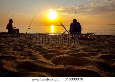 Two Buddies Are Catching Fish From The Sandy Beach With Fishing Rods, Sunrise Morning Over Mediterra