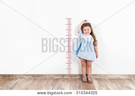 Little Blond Girl Measuring Height On White Wall