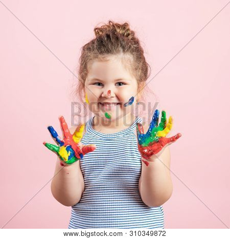 Smiling Little Girl With Hands In The Paint On Pink Background.