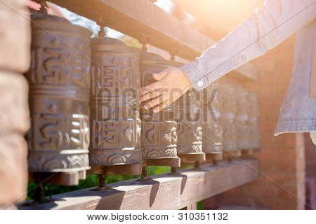 Photo of Chinese prayer drums and human hands