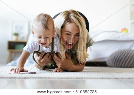 Horizontal Image Of Joyful Cheerful Young Caucasian Female With Blonde Hair Chasing After Her Adorab