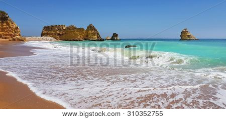 Beautiful Landscape: Cliffs In Turquoise Atlantic Ocean On The Beach Praia Dona Ana, Lagos, Portugal
