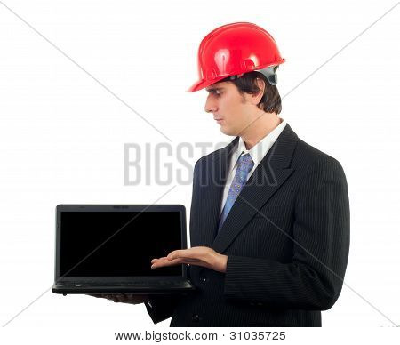 Young engineer in business suit and with red helmet on his head showing your content on the notebook