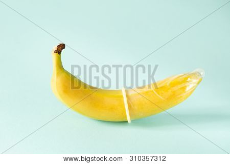 Sex Education Concept - Banana In Condom On Pastel Background, Copy Space