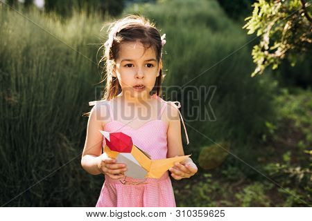 Cute Little Girl Holding Paper Colorful Bird In The Park. Curious Child Playing With A Bird Toy Outd