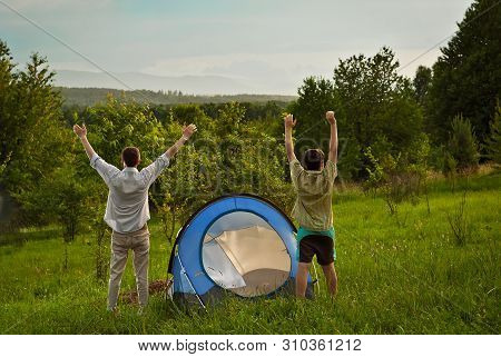 Guys Lay A Tent On The Grass.the Men Raised Their Hands Up And Looked At The Sunset. Forest And Moun