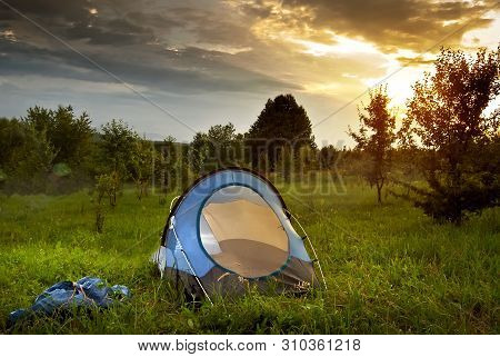 Tent On The Grass. Forest And Mountains In The Background. The Sun Comes In And The Sky Is Yellow. T
