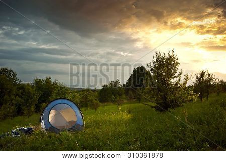 Guys Lay A Tent On The Grass. Forest And Mountains In The Background. The Sun Comes In And The Sky I