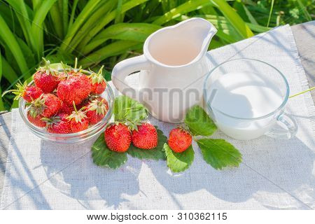 Strawberry Berries And Leaves, A Jug And A Cup With Milk On A Napkin On A Wooden Table