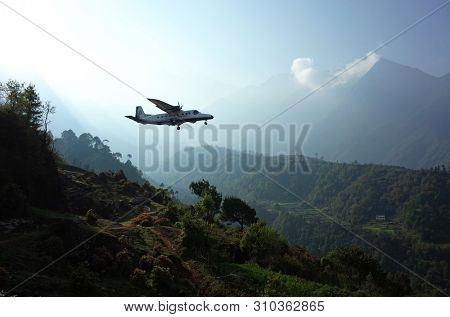 Lukla, Nepal - May 8, 2019: Small propeller airplane taking off from Tenzing–Hillary Airport on background of green Himalaya Mountains in morning light
