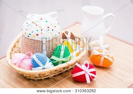 Knitted Easter Eggs And A Cake In A Basket On A Napkin On The Table