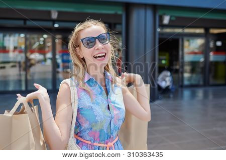 Portrait Of An Excited Beautiful Girl Wearing Dress And Sunglasses Holding Shopping Bags In Front Of