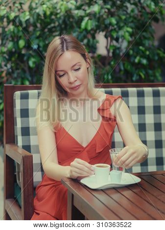Beautiful European Lady In A Red Dress Is Sitting In The Stylish Street Cafe And Drinking Delicious