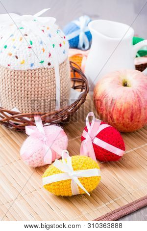 Knitted Easter Eggs And Cake In A Basket And Jug On A Wooden Table