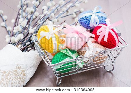 Knitted Easter Eggs Tied With Colored Ribbons In A Metal Basket And Willow On A Wooden Table