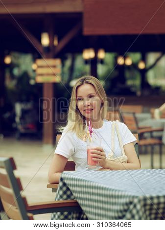 Cheerful Smiling Girl Enjoying Strawberry Smoothie In Street Bar.