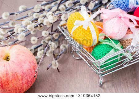 Knitted Easter Eggs Tied With Colored Ribbons In A Metal Basket, An Apple And Willow On A Wooden Tab