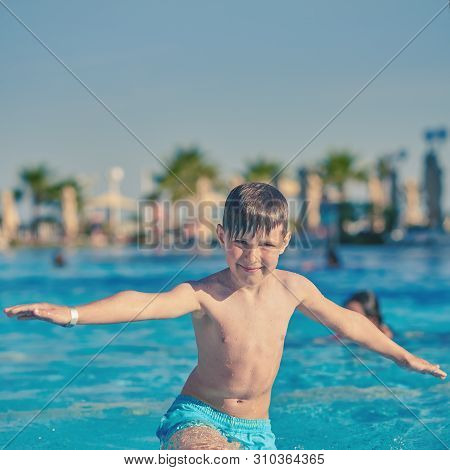 Portrait Of Smiling Caucasian Boy Spending Time In Pool At Resort. He Is Enjoying His Summer Holiday
