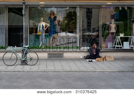 Munich, Bavaria, Germany - May 29, 2019.  Very Sad Looking Homeless Man With A Dog And A Sign Asking