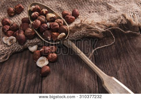Hazelnuts On An Old Spoon And Composition From Old Wood And Material