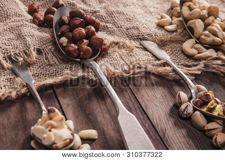 Close-up On Different Kinds Of Nuts On Old Spoons And Composition From Old Wood And Material