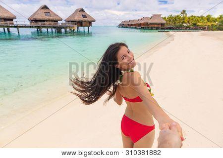 Follow me couple selfie picture on romantic honeymoon holiday at Luxury Bora Bora resort vacation. Asian bikini woman smiling walking on beach.