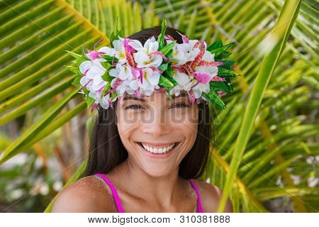 Tahiti flower crown hei po'o smiling woman wearing tahitian headpiece wreath cultural decoration. Bora Bora, French Polynesia. Beauty Asian multiracial model smile on palm tree background.