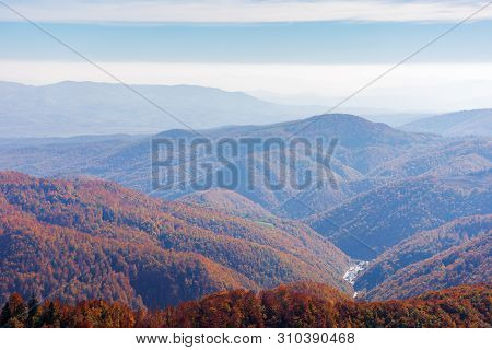 Beautiful Autumn Nature Background. Blue Sky With Clouds Above The Mountains. Forested Hills In Redd