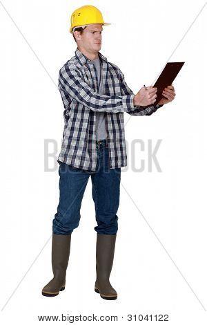 Incredulous tradesman looking at a clipboard