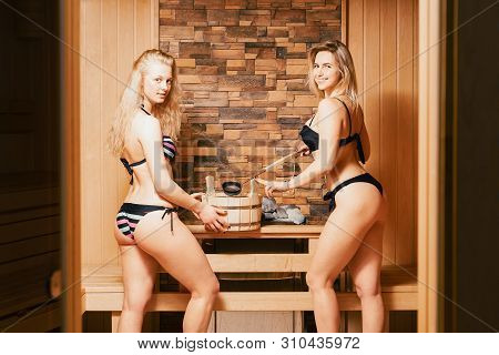 Finnish Sauna. Two Young Girls Blondes In Bathing Suits Bathe In The Bath. A Woman Takes Water In A