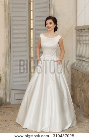 Young Bride In White Silk Wedding Dress. Full-lenght Vertical Portrait.