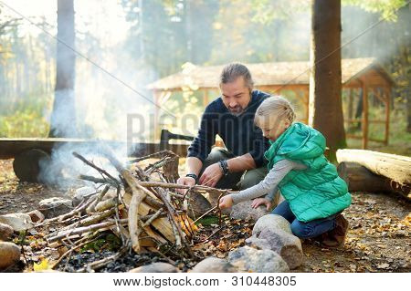 Cute Young Girl Learning To Start A Bonfire. Father Teaching Her Daughter To Make A Fire. Child Havi
