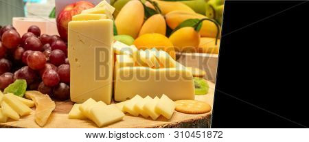 edam cheese with variety of fruit and cracker on wooden plate in buffet line, panoramic Large Leaderboard crop size
